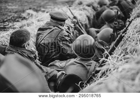 Re-enactors Dressed As World War Ii Russian Soviet Red Army Soldiers Hidden Sitting In Trench. Photo
