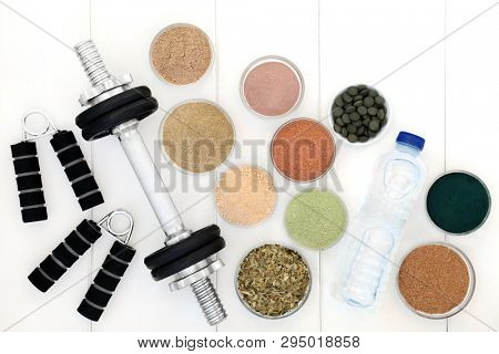 Body building equipment of weights and hand grippers, dietary supplement powders and chlorella tablets and with ginkgo green tea and fresh water. Top view.