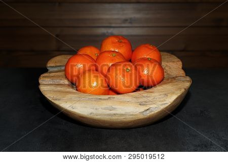 Pile Of Tangerines In A Wooden Bowl On Dark Table. Torfhaus, Germany