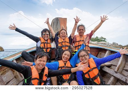 Traveler Group That Are Large Family In Life Vest Raise Hands With Happy And Enjoy On The Boat While