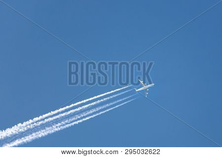 High-flying Airplane On The Clear Blue Sky Leaving White Trace Behind, Bottom View, Copy Space/ Airc