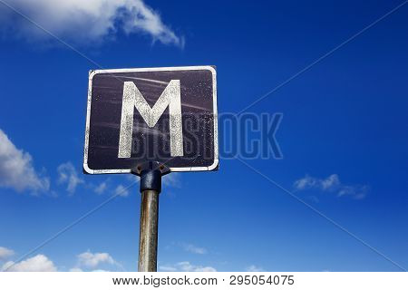 Weathered Road Sign With The Capital Letter M, For Meeting Point, Against A Blue Cloudy Sky. Common