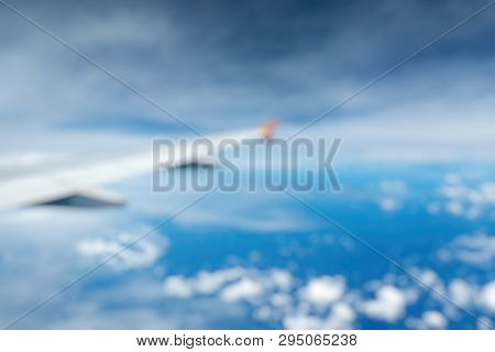 Out Of Focus Of Wing Of An Airplane Flying Above The Clouds See Through The Window. Business Concept