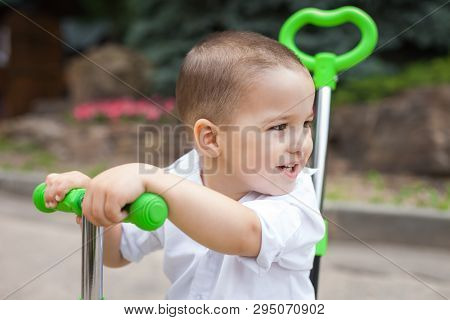 Lovely Small Child Boy Riding A Green Trike In The Park. Concept Of Happy Childhood