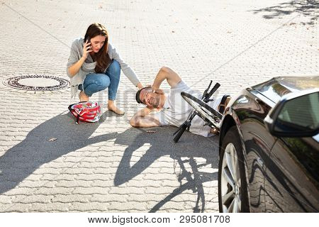 Young Woman Calling Ambulance After Hitting Male Bicyclist Accidentally With Her Car