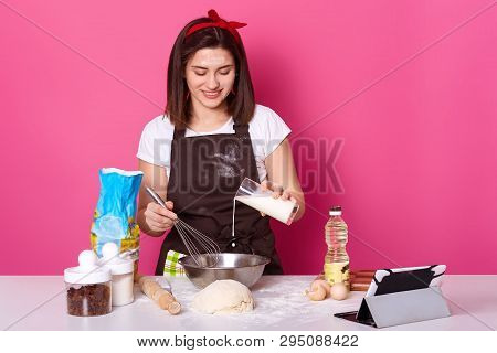 Beautiful Brunette Female Pours Milk Into Plate. Chef Kneads Dough, Preparing For Easter Holiday, Ma