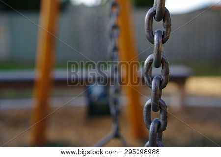 Close up view of chain hung horizontally with other chains blurred in background poster