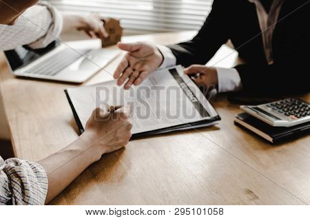 Hand Of Young Man Customer Signing Contract For Buying House With Real Estate Broker In Suit At Esta