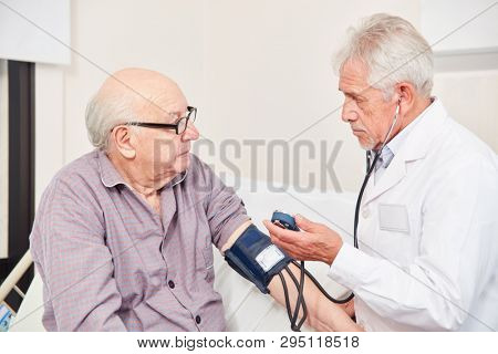 Doctor measuring blood pressure in an old man as a control in hypertension