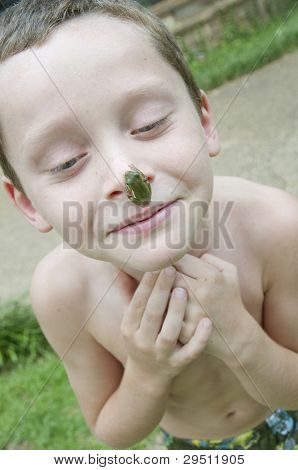 silly boy with frog hanging from nose