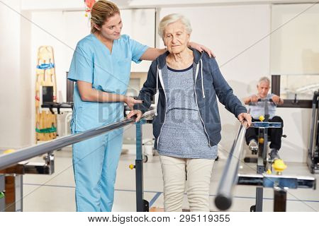 Rehabilitation therapist supports senior woman on treadmill in physiotherapy