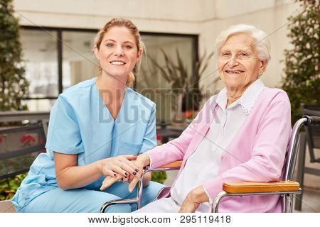 Caring geriatric nurse and happy senior woman in wheelchair at nursing home