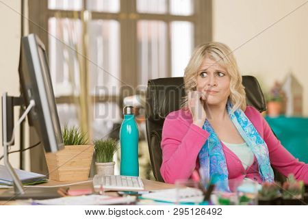 Worried Professional Woman Wearing Pink Sweater In Her Office