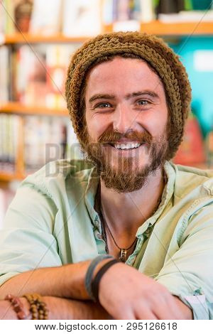Smiling Young Man With Knit Cap In Book Store Or Library