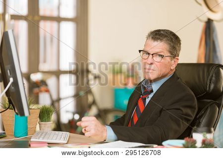 Skeptical Man Working At His Desk In Sunlit Office