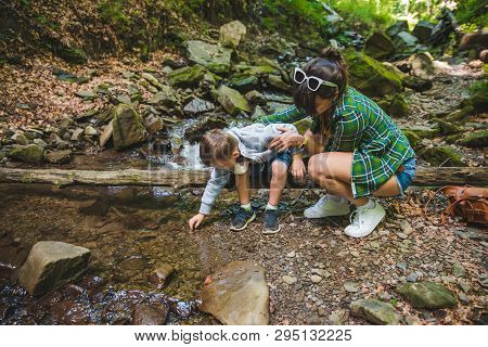 Mother With Kid Near Mountains River. Care Concept