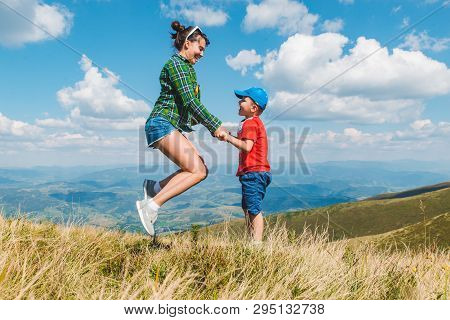Mother With Son Jumping On Top Of Mountain. Beautiful Landscape View. Travel Hiking Concept