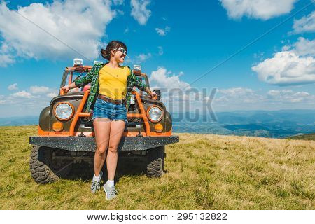 Woman Near Off Road Cur At The Top Of The Mountain. Beautiful View On Background. Copy Space. Sunny