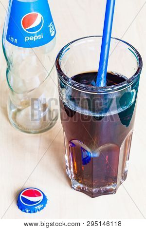 Moscow, Russia - April 4, 2019: Pepsi Soft Drink In Glass With Blue Drinking Tube, Used Crown Cap An