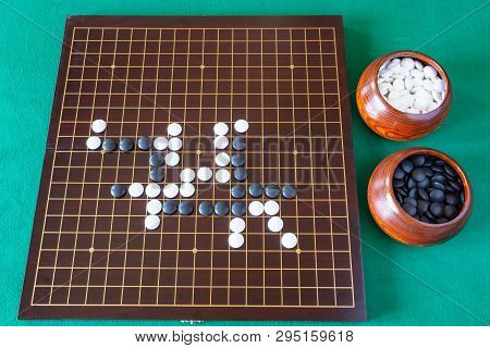 Top View Of Gameplay Of Go Game And Playing Stones In Bowls And Wooden Board On Green Table