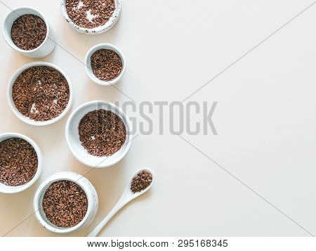 Flax Seeds On White Or Light Beige Background. Set Of Small Bowls With Organic Flax Seed Or Linen Se