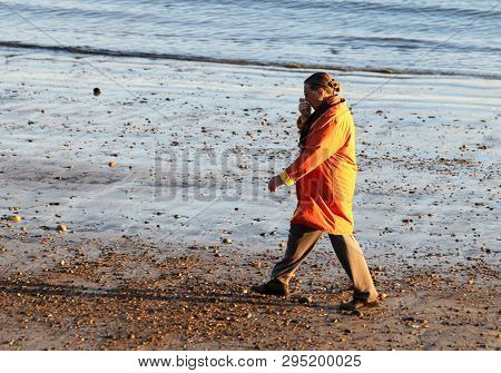 Gloucester, Massachusetts - April 6, 2019: A Woman In The Orange Coat Walking On The Beach At Early