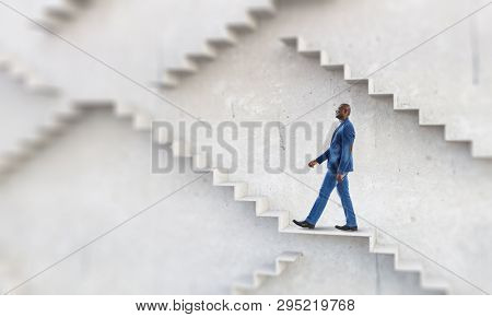 Black businessman climbing stone stairs illustrating career development and success concept. Mixed media