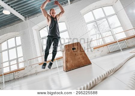 Dynamic Shot Of Fitness Male Athlete Jumping Through At Square Box In Cross Gym. Strong Man Doing Ju