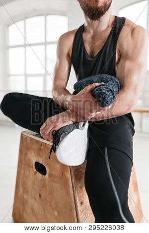 Close Up View On Strong Male Athlete Resting On Wooden Box After Cross Intense In Workout Gym. Fit P