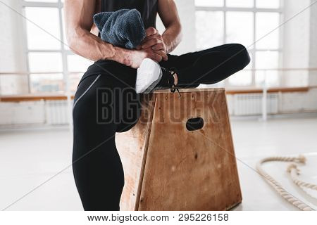 Perspiring Male Athlete Resting After Hard Workout In Light Gym. Strong Sweaty Man Sitting At Box An