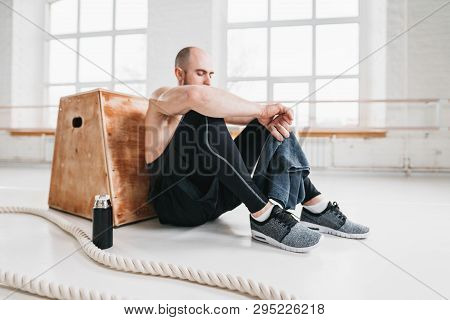 Side View Of Tired Strong Man Sitting On Box At Gym. Perspiring Fit Sportsman Resting With Towel Aft