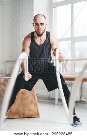 Fit Man Athlete Using Battle Ropes For Exercising At Light Sport Hall. Strong Fitness Sportsman Usin