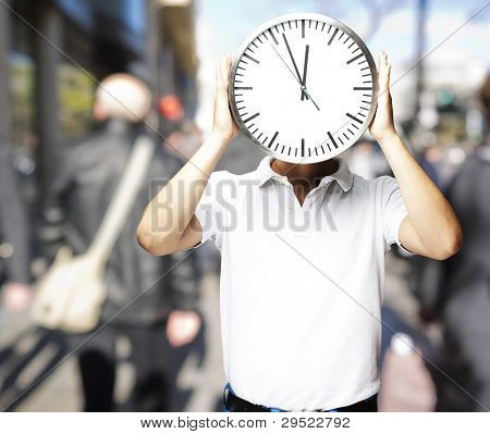 portrait of a man holding a big clock in front of his head at a crowded place