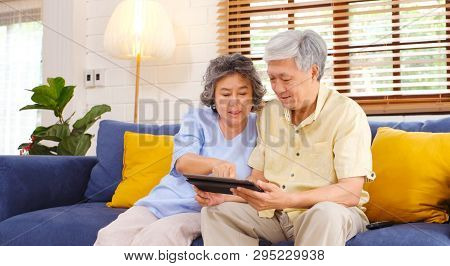 Happy Senior Asian Couple Using Digital Tablet Computer Sitting On Sofa At Home Living Room Backgrou