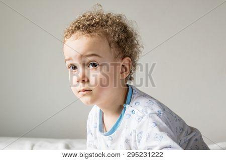 Blonde Boy In Bright Pajamas On The White Carpet