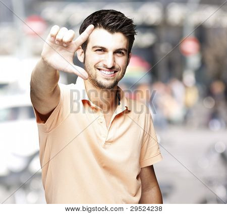 portrait of a handsome man doing a good symbol against a crowded city background