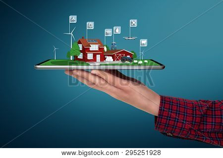 Farmer Holds A Tablet With A Modern Smart Farm Using Renewable Energy And Drones. Digital Transforma