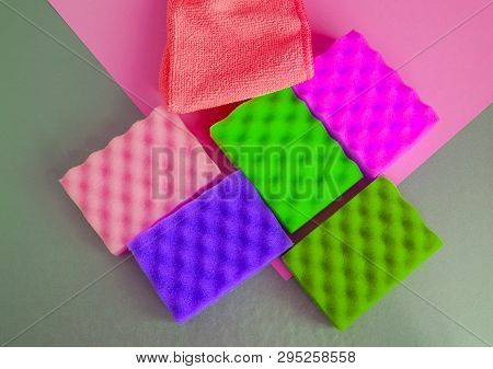 A set of multi-colored sponges and rags for cleaning and cleanliness on a gray background, the concept of outsourcing cleaning company, top View poster