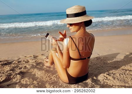 Sun Protection, Girl Using Sunscreen To Safe Her Skin Healthy. Sexy Young Woman In Bikini Holding  B