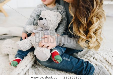 Beautiful Young Mother Holding Her Cute Son And A Teddy Bear
