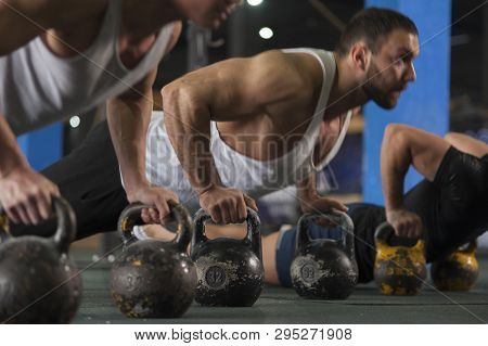 Close-up - Group Of Athletic Men Training Push Ups In Gym. Strong Muscular Athletes During Workout W