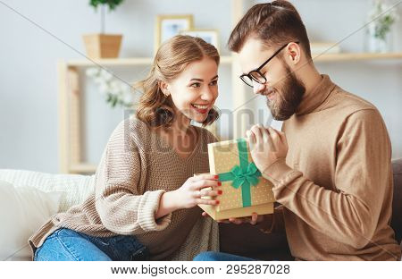 Happy Married Couple Man And Woman Give A Gift For The Holiday