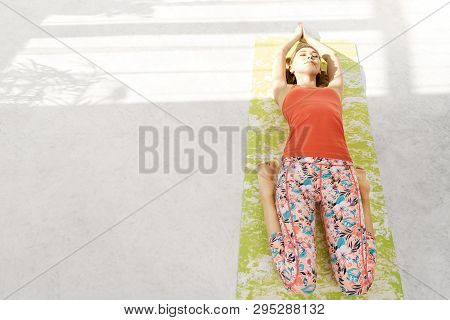 Photo Of Beautiful Young Woman Lying On A Yoga Mat, Resting After Doing Yoga Exercises, Lying In Sav
