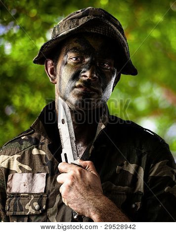 portrait of a young soldier threatning to suicide against a wild background