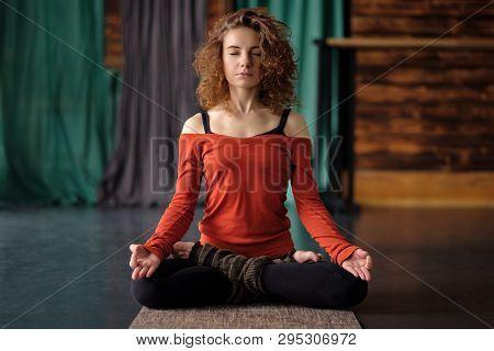 Yoga Girl Sitting In Lotus Pose Or Padmasana. Practicing On Mat