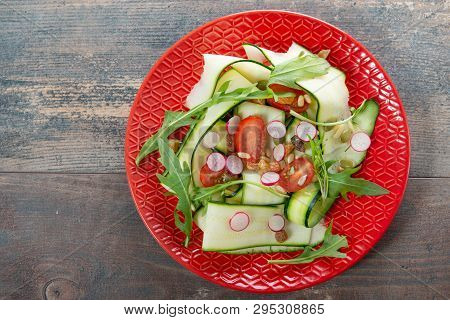 A Red Plate With Vegetarian Salad Of Natural Organic Vegetables