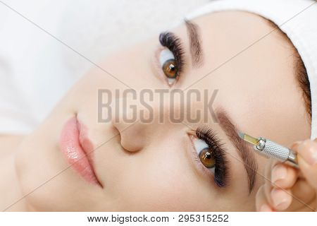 Beautiful Young Girl With Long Eyelashes Tweezing Her Eyebrows In A Beauty Salon. Eyebrow Correction