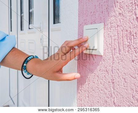 Woman Hand Ringing On Doorbell Near Pvc Front Door