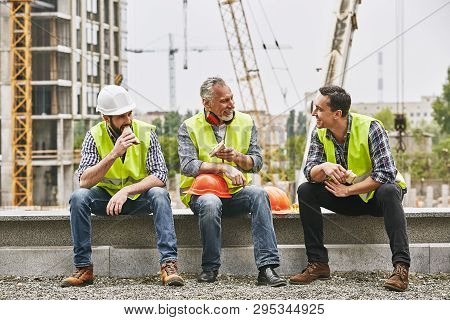 Time For A Break. Group Of Builders In Working Uniform Are Eating Sandwiches And Talking While Sitti