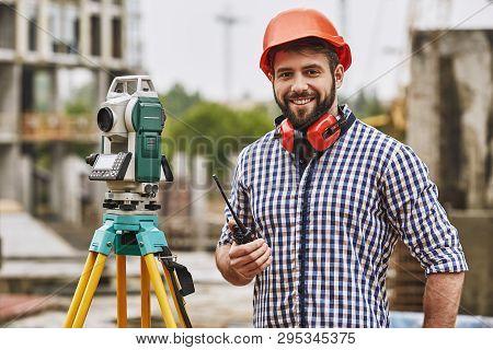 Surveyor Equipment. Surveyor Engineer In Protective Wear And Red Helmet Using Geodetic Equipment, Ho